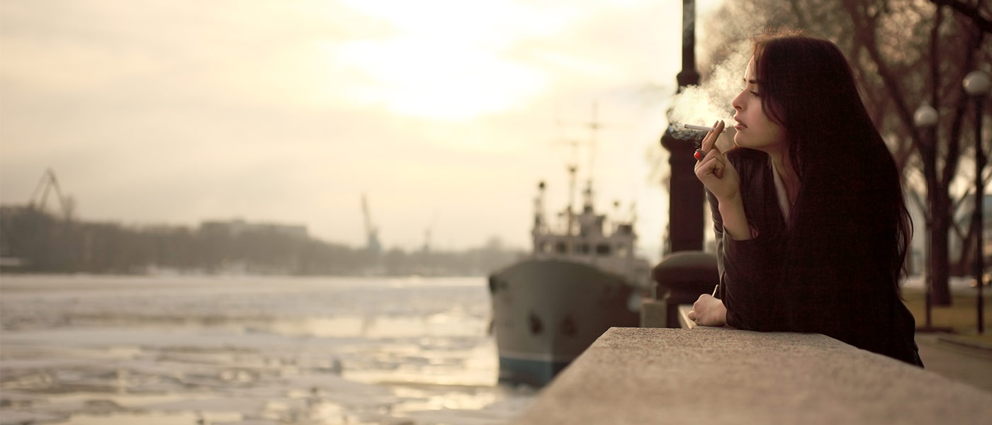 Photo of a young woman smoking alongside a waterway