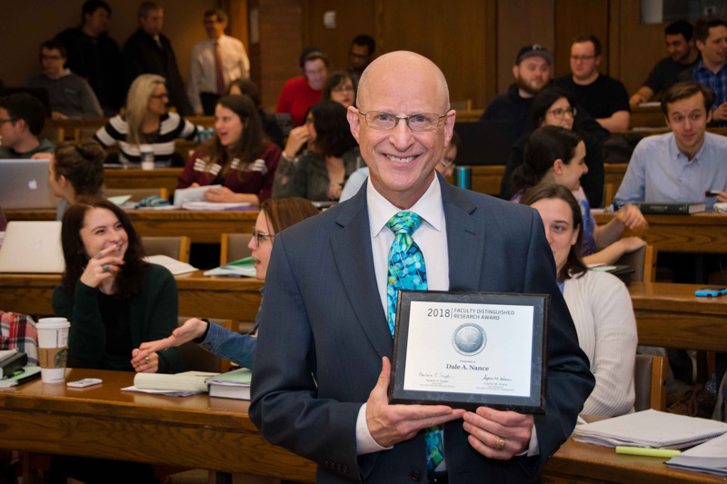 Photo of Dale Nance holding Faculty Distinguished Research Award plaque