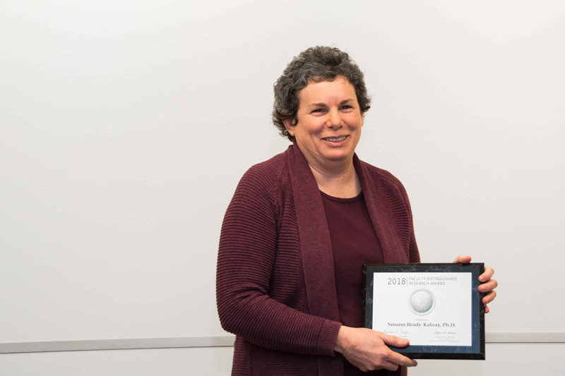 Photo of Susann Brady-Kalnay holding Faculty Distinguished Research Award plaque
