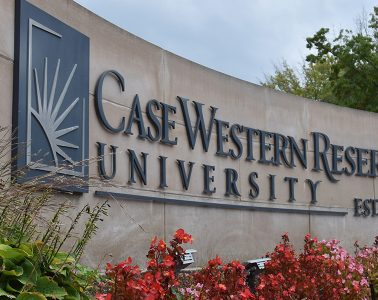 Photo of Case Western Reserve University signage with flowers in front of it