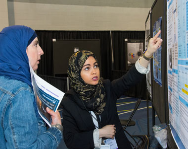 Photo of researcher explaining her poster to a colleague.