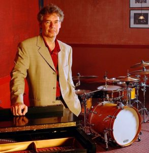 Bill Bruford next to a drumset