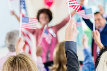 stock image of a crowd applauding a female political candidate