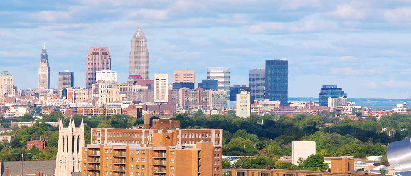Photo of the Cleveland skyline with buildings and trees in the foregound