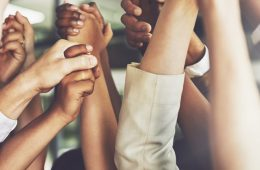 Close-up of group of individuals holding hands in air