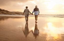 Two elderly people holding hands and walking on the beach as the sun sets