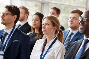 people listening to a speaker at a conference