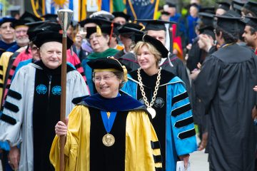 Photo of Robin Dubin leading the academic procession at commencement