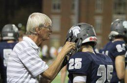 Hugh Marshall helps a CWRU football player with his helmet