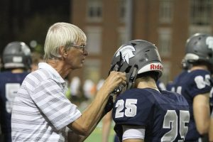 Hugh Marshall helps a CWRU football player with his helmet