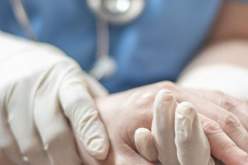 Close up on doctor with gloves holds patient's hand
