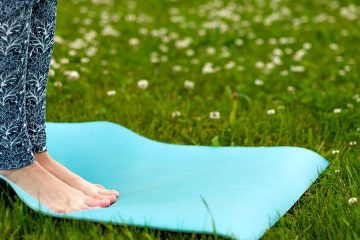 Photo of a woman standing on a yoga mat outside