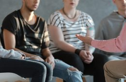 Photo of young people sitting in group therapy