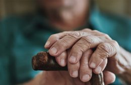 Close up photo showing an elderly person's hands on a cane
