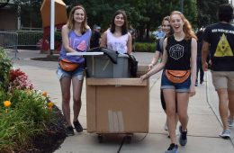 Four Case Western Reserve University students smiling as they move boxes on move-in day