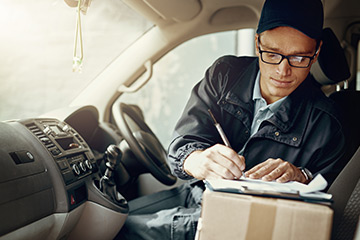 Delivery person in front of vehicle writing on clipboard with package in passenger seat