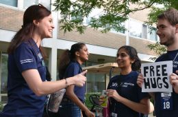 "Natalie Nielsen talks to fellow Case Western Reserve University orientation leaders, while one male student holds sign that says ""Free Hugs"""