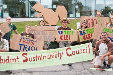 Members of the Student Sustainability Council pose for photo and hold signs at homecoming parade