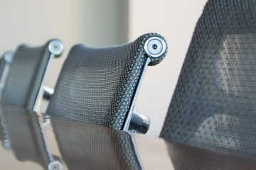 Row of office chairs lined up at conference table