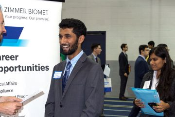 Student talks to employer at Career Fair with students lined up behind him