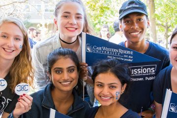 Six Case Western Reserve University students pose for photo and hold CWRU gear