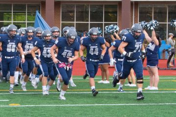 Case Western Reserve University football team runs on to field during 2017 homecoming game