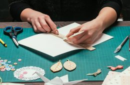 Close up photo on hands of someone making a card with craft supplies on table