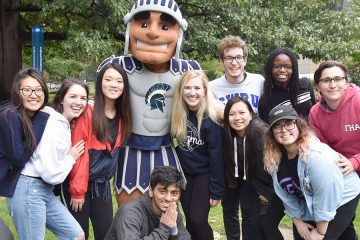 A group of Case Western Reserve University students pose for photo with Spartie the mascot during homecoming