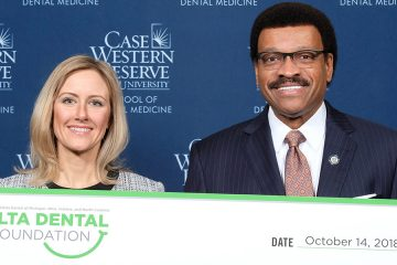 Dean Kenneth Chance holds presentation check with a Delta Dental representative