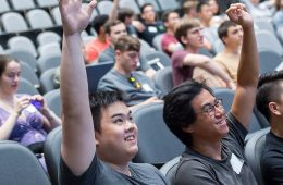 Two male students raise their hands in a lecture hall class