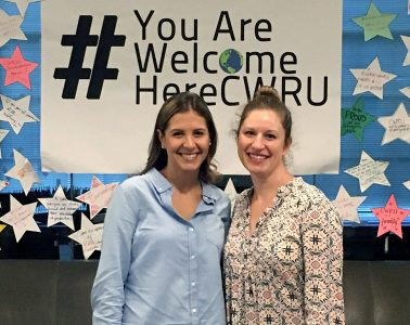 Oriana Trejo and Sara Spiegler pose for photo in front of #YouAreWelcomeHere sign