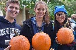Three Case Western Reserve University students pose for photo while holding pumpkins during homecoming