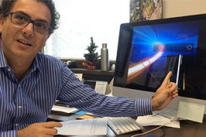 professor Giuseppe Strangi talking at his desk,