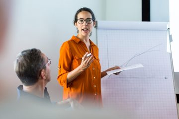 Woman stands in front of large notepad giving a presentation