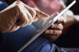 a senior citizen working on a computer tablet