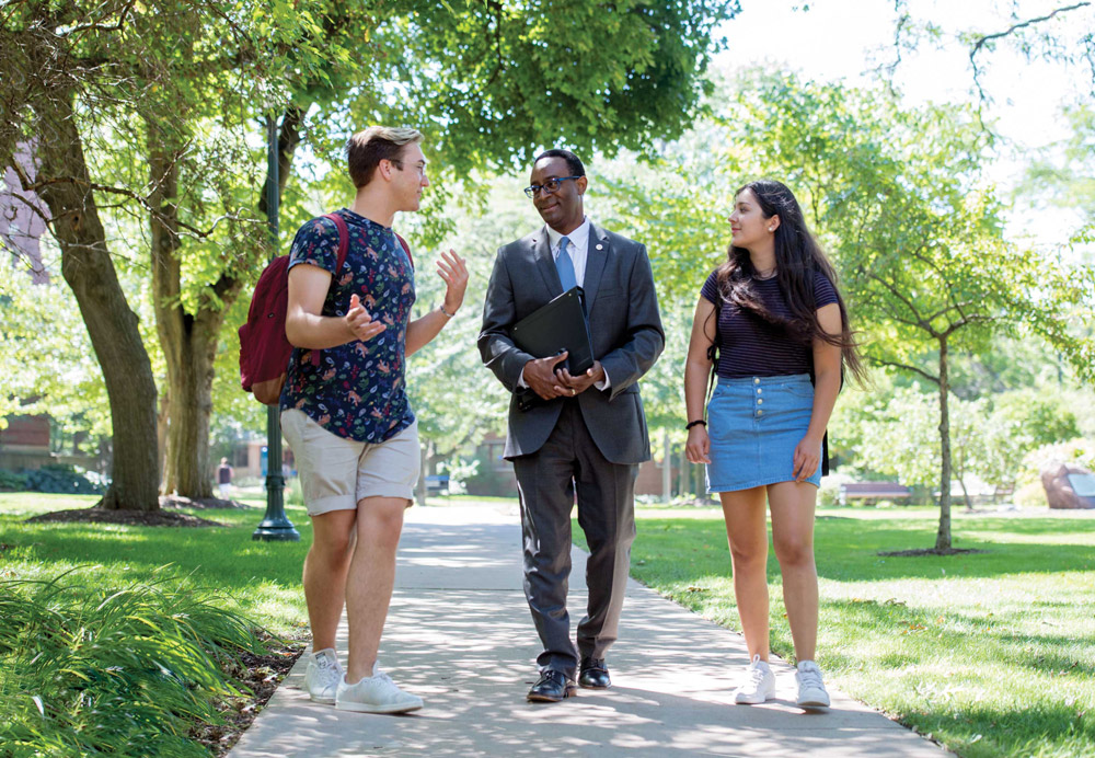 Provost Ben Vinson III walks across campus with two students