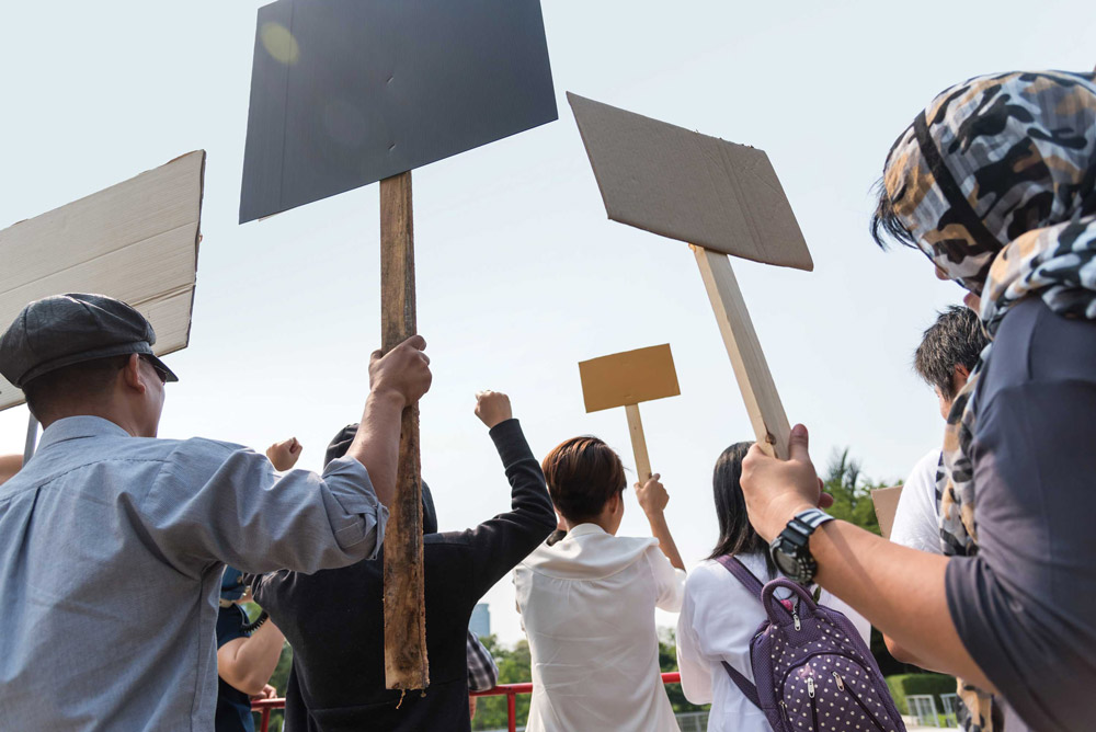 Photo taken behind protesters holding signs up