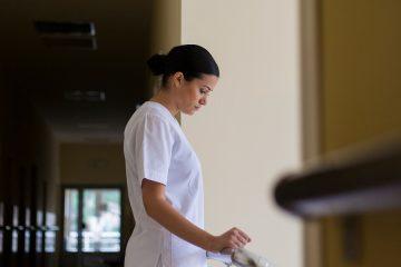 nurse standing in a hallway, looking contemplative