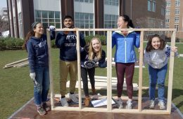 Five students gather for a photo next to a house frame