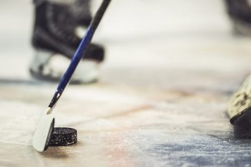 Close up of hockey puck and sticks during ice hockey game