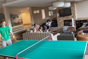 Two CWRU students play ping pong while others gather around on couches in residence hall