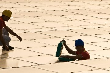 men installing solar panels on top of a building