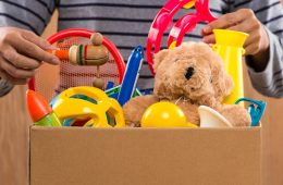 Photo of a man putting toys in a box
