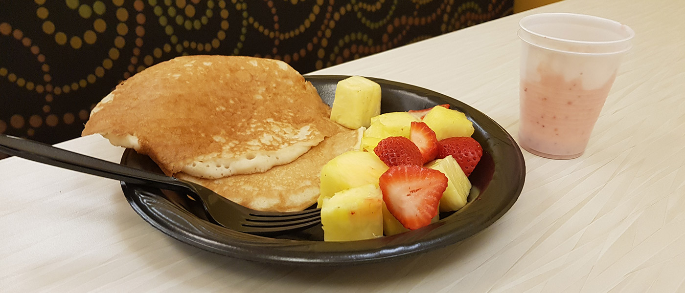 A plate with pancakes and fruit next to a cup with a smoothie sitting on table at Late Night Breakfast