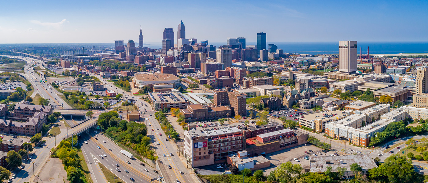 Photo of the Cleveland skyline with buildings in the foreground and Lake Erie in the background
