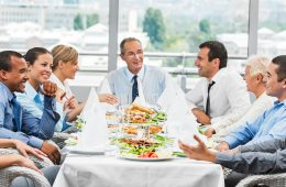 group of businesspeople eating lunch at a long table