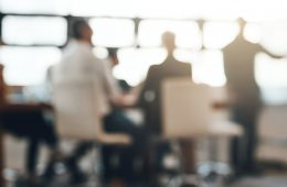 A blurred photo of people sitting around a table at a business meeting