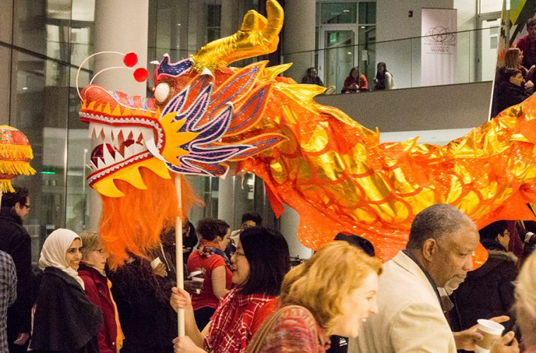 A student holds up a large dragon puppet in a crowd at a Lunar New Year event at CWRU