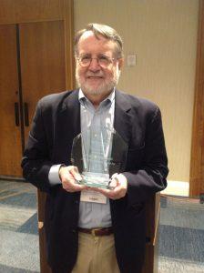 Photo of Paul Giannelli holding lifetime achievement award