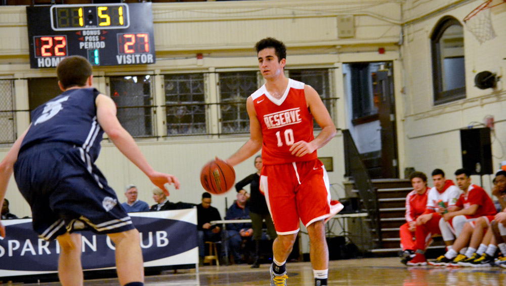 Photo of a men's basketball player wearing a Western Reserve University jersey dribbling the ball during a throwback game